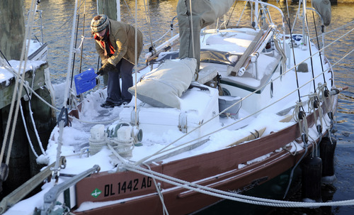 Erin Maloney of Annapolis, Md., clears snow off of her boat docked  at the Annapolis City Dock, Wednesday, Jan. 22, 2014. Residents along the Mid-Atlantic are digging out after a massive winter storm packing up to a foot of snow, strong winds and icy temperatures slammed into the region. (AP Photo/Susan Walsh)