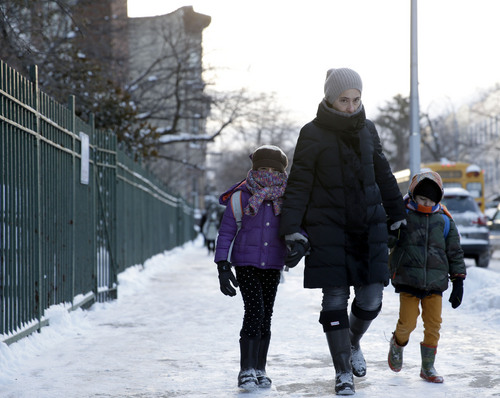 Parents and children arrive to school bundled up against the cold in the Brooklyn borough of New York, Wednesday, Jan. 22, 2014.  A winter storm stretched from Kentucky to New England and hit hardest along the heavily populated Interstate 95 corridor between Philadelphia and Boston. Snow began falling at midmorning Tuesday in Philadelphia and dumped as much as 14 inches by Wednesday morning, with New York seeing almost as much.  Boston and Philadelphia officials ordered schools closed Wednesday, but in New York City, the nation's largest public school system remained open. (AP Photo/Seth Wenig)