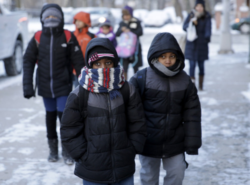 Children arrive to school bundled up against the cold in the Brooklyn borough of New York, Wednesday, Jan. 22, 2014.  A winter storm stretched from Kentucky to New England and hit hardest along the heavily populated Interstate 95 corridor between Philadelphia and Boston. Snow began falling at midmorning Tuesday in Philadelphia and dumped as much as 14 inches by Wednesday morning, with New York seeing almost as much.  Boston and Philadelphia officials ordered schools closed Wednesday, but in New York City, the nation's largest public school system remained open. (AP Photo/Seth Wenig)
