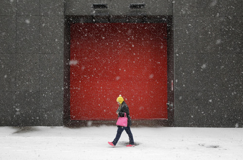 A woman walks outside of an office building as snow falls, Tuesday, Jan. 21, 2014, in Baltimore. Thousands of flights were canceled, students got an extra day off from school or were being sent home early, and the federal government closed its offices in the Washington area Tuesday as another winter storm bore down on the Mid-Atlantic and Northeast. (AP Photo/Patrick Semansky)