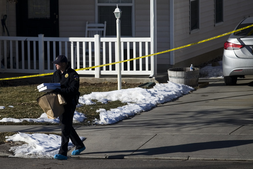 Investigators remove evidence from a home, Friday, Jan. 17, 2014, in Spanish Fork, Utah,  where five people were found dead on Thursday.  A 34-year-old officer shot and killed his wife, mother-in-law and two young children and turned the gun on himself, authorities said Friday.  Spanish Fork police said the five were found dead about 11 p.m. Thursday, when co-workers reported Joshua Boren didn't show up for his night shift as a patrol officer at the Lindon Police Department. (AP Photo/Daily Herald, Mark Johnston)
