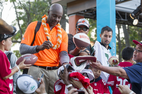 Jerry Rice, left, alumni captain of Team Rice, signs autographs for fans at the end of day two of the NFL football Pro Bowl draft, Wednesday, Jan. 22, 2014, in Kapolei, Hawaii. (AP Photo/Eugene Tanner)