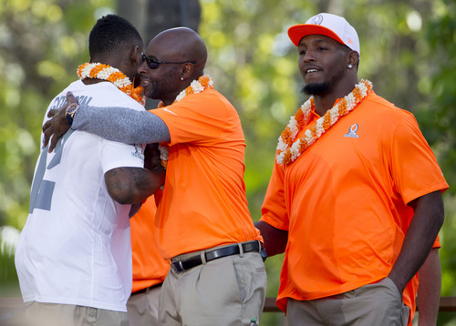 Cleveland Browns wide receiver Josh Gordon, left, is greeted by Jerry Rice, center, and St. Louis Rams defensive end Robert Quinn, right, after Rice selected Gordon for his team in the Pro Bowl draft, Wednesday, Jan. 22, 2014, in Kapolei, Hawaii. (AP Photo/Eugene Tanner)