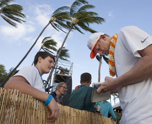 Andrew Pruett, left, of Charlotte, N.C., watches as St. Louis Rams punter Johnny Hekker signs his autograph book during day two of the NFL football Pro Bowl draft, Wednesday, Jan. 22, 2014, in Kapolei, Hawaii. (AP Photo/Eugene Tanner)