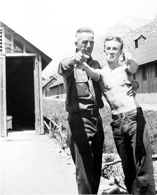 Photo Courtesy Utah State Historical Society  Image shows a shirtless enrollee and a CCC foreman posing for a humorous photograph outside a latrine or shower building at what is likely the NP-2, Zion CCC Camp between 1933-42.