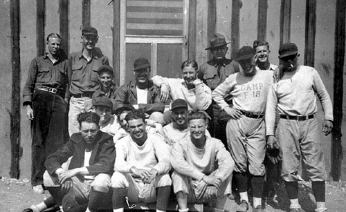 """Photo Courtesy Utah State Historical Society  Image shows a crew of CCC enrollees, most of whom are in baseball uniforms, posing for a group photograph. One man is wearing a shirt that says, """"Camp F-18."""" F-18 was the Blue Springs CCC Camp in Escalante, Garfield County, Utah."""