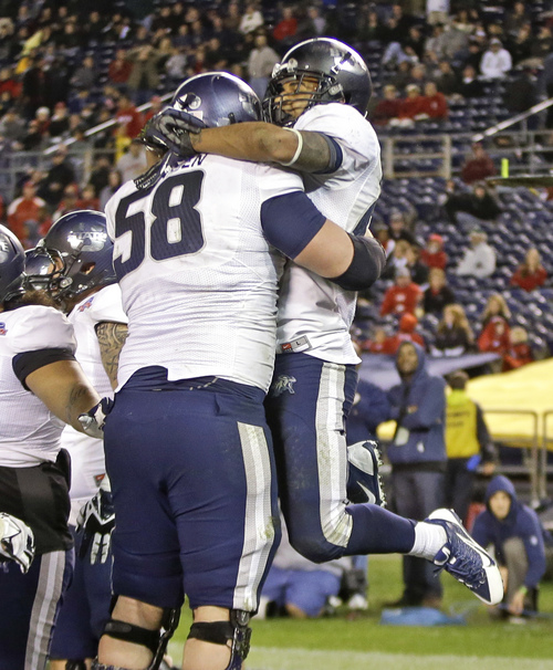Utah State's Joey DeMartino is lifted by Tyler Larsen after his one yard touchdown run in Utah State's 21-14 victory over Northern Illinois in the Poinsettia Bowl NCAA college football game, Thursday, Dec. 26, 2013, in San Diego. (AP Photo/Lenny Ignelzi)