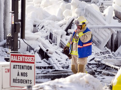 """An emergency worker walks past a sign that reads """"Look out for our residents"""" as they search through the icy rubble of a fire that destroyed a seniors' residence Friday, Jan. 24, 2014, in L'Isle-Verte, Quebec. Five people are confirmed dead and 30 people are still missing, while with cause of Thursday morning's blaze is unclear police said. Authorities are using steam to melt the ice and to preserve any bodies that are buried. (AP Photo/The Canadian Press, Ryan Remiorz)"""
