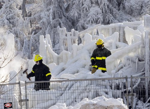 Rescue personnel search through the icy rubble of fire that destroyed a seniors' residence Friday, Jan. 24, 2014, in L'Isle-Verte, Quebec. Five people are confirmed dead and 30 people are still missing, while with cause of Thursday morning's blaze is unclear police said. Authorities are using steam to melt the ice and to preserve any bodies that are buried. (AP Photo/The Canadian Press, Ryan Remiorz)