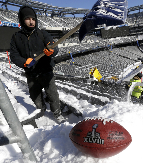 A football with the Super Bowl XLVIII logo is set on a mound of snow as an for an NFL photographer to make photos of it as workers shovel snow off the seating area at MetLife Stadium as crews removed snow ahead of Super Bowl XLVIII following a snow storm, Wednesday, Jan. 22, 2014, in East Rutherford, N.J. Super Bowl XLVIII, which will be played between the Denver Broncos and the Seattle Seahawks on Feb. 2, will be the first NFL title game held outdoors in a city where it snows. (AP Photo/Julio Cortez)