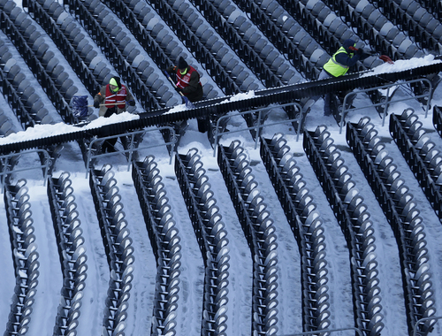 Workers shovel snow from the seats at MetLife Stadium as crews removed snow ahead of Super Bowl XLVIII following a snow storm, Wednesday, Jan. 22, 2014, in East Rutherford, N.J. Super Bowl XLVIII, which will be played between the Denver Broncos and the Seattle Seahawks on Feb. 2, will be the first NFL title game held outdoors in a city where it snows. (AP Photo/Julio Cortez)
