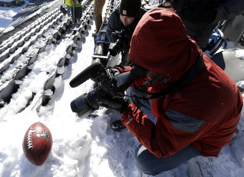 Bergen Record newspaper photographers Tyson Trish, left, and Thomas Franklin, shoot images of a football with the Super Bowl XLVIII logo  set on a mound of snow as workers shovel snow off the seating area at MetLife Stadium as crews removed snow ahead of Super Bowl XLVIII following a snow storm, Wednesday, Jan. 22, 2014, in East Rutherford, N.J. Super Bowl XLVIII, which will be played between the Denver Broncos and the Seattle Seahawks on Feb. 2, will be the first NFL title game held outdoors in a city where it snows. (AP Photo/Julio Cortez)