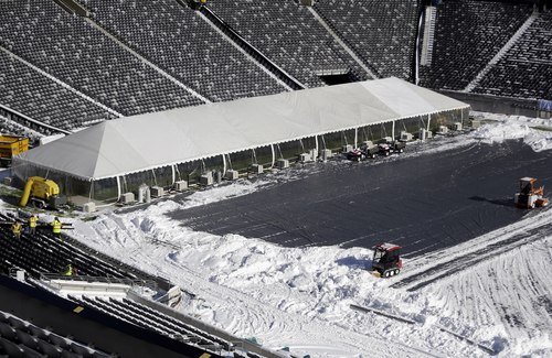 Workers driving small tractors, right, plow snow off a tarp covering the field at MetLife Stadium as a tent protects the end zone area ahead of Super Bowl XLVIII as crews removed snow following a snow storm, Wednesday, Jan. 22, 2014, in East Rutherford, N.J. Super Bowl XLVIII, which will be played between the Denver Broncos and the Seattle Seahawks on Feb. 2, will be the first NFL title game held outdoors in a city where it snows. (AP Photo/Julio Cortez)