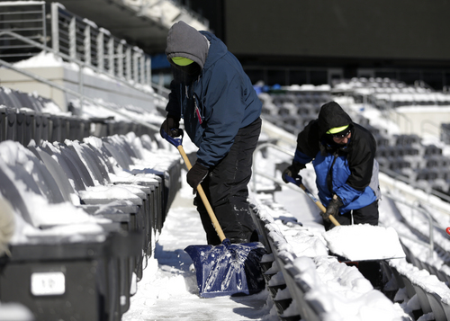 Workers shovel snow off the seates at MetLife Stadium as crews removed snow ahead of Super Bowl XLVIII following a snow storm, Wednesday, Jan. 22, 2014, in East Rutherford, N.J. Super Bowl XLVIII, which will be played between the Denver Broncos and the Seattle Seahawks on Feb. 2, will be the first NFL title game held outdoors in a city where it snows. (AP Photo/Julio Cortez)