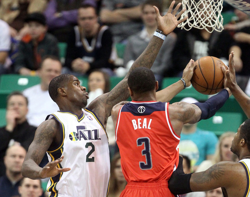 Utah Jazz's Marvin Williams (2) defends as Washington Wizards' Bradley Beal (3) drives to the basket during the first quarter of an NBA basketball game Saturday, Jan. 25, 2014, in Salt Lake City. (AP Photo/Rick Bowmer)