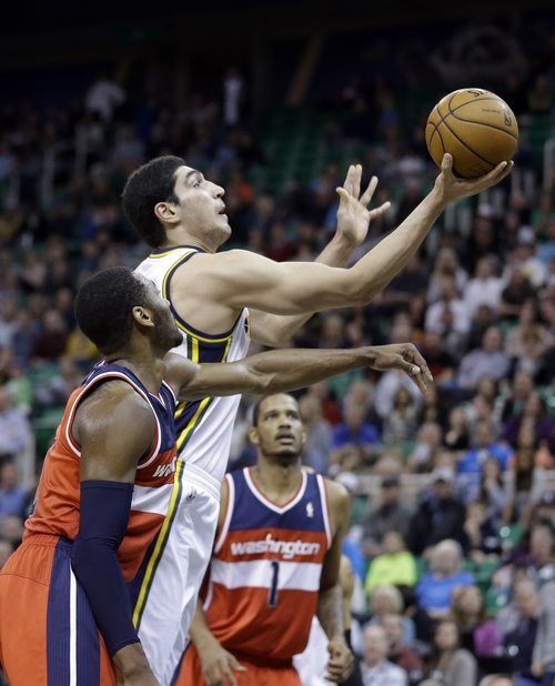 Utah Jazz's Enes Kanter, center, lays the ball up as Washington Wizards' John Wall, left, and Trevor Ariza (1) watch during the fourth quarter of an NBA basketball game Saturday, Jan. 25, 2014, in Salt Lake City. The Jazz won 104-101. (AP Photo/Rick Bowmer)