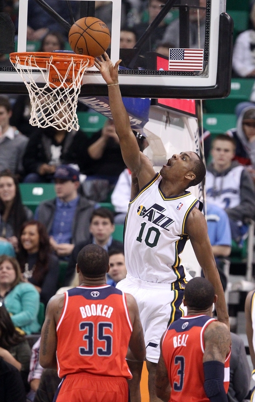 Utah Jazz's Alec Burks (10) lays the ball in as Washington Wizards' Trevor Booker (35) and teammate Bradley Beal (3) look on in the third quarter during an NBA basketball game Saturday, Jan. 25, 2014, in Salt Lake City. The Jazz won 104-101. (AP Photo/Rick Bowmer)