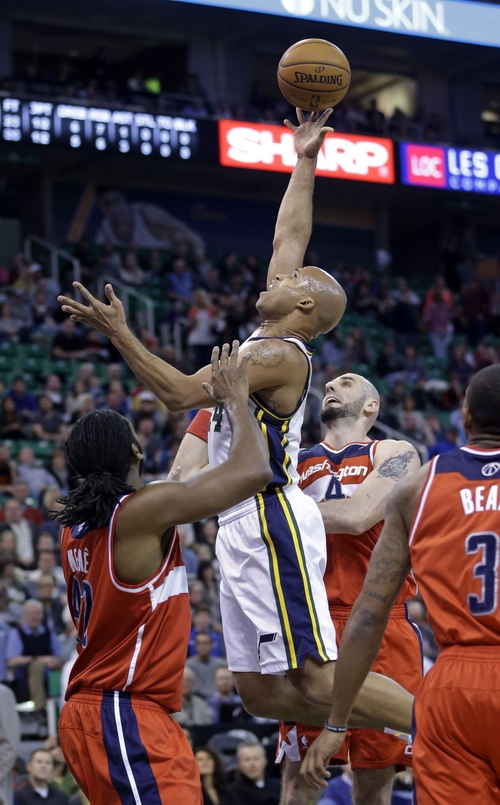 Utah Jazz's Richard Jefferson, center, lays the ball up as Washington Wizards' Nene, left, and tMarcin Gortat (4), of Poland, defend during the first quarter of an NBA basketball game Saturday, Jan. 25, 2014, in Salt Lake City. (AP Photo/Rick Bowmer)