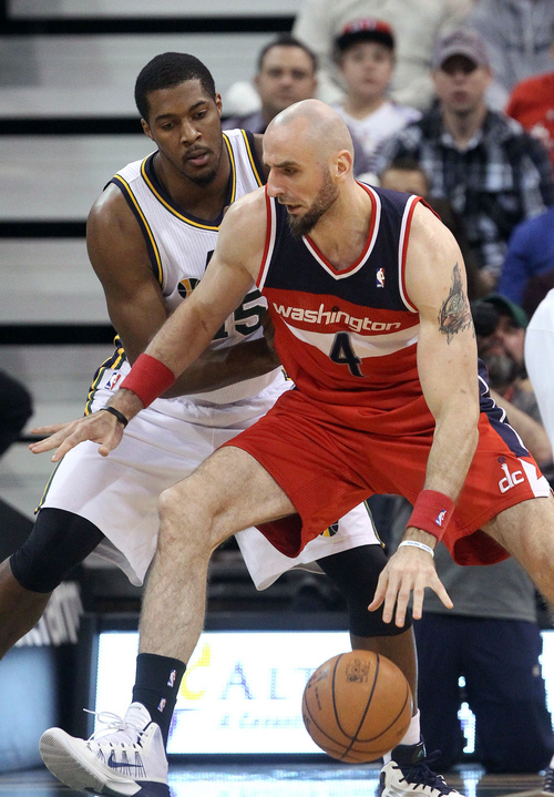 Washington Wizards' Marcin Gortat (4) of Poland, drives as Utah Jazz's Derrick Favors, rear, defends during the first quarter of an NBA basketball game Saturday, Jan. 25, 2014, in Salt Lake City. (AP Photo/Rick Bowmer)