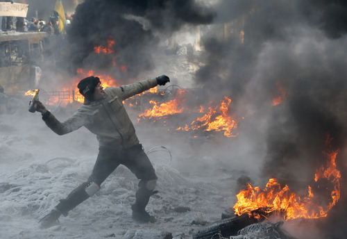 A protester throws a Molotov cocktail towards riot police during a clash in central Kiev, Ukraine, Saturday Jan. 25, 2014. Ukraine's Interior Ministry has accused protesters in Kiev of capturing two of its officers as violent clashes have resumed in the capital and anti-government riots spread across Ukraine. (AP Photo/Efrem Lukatsky)