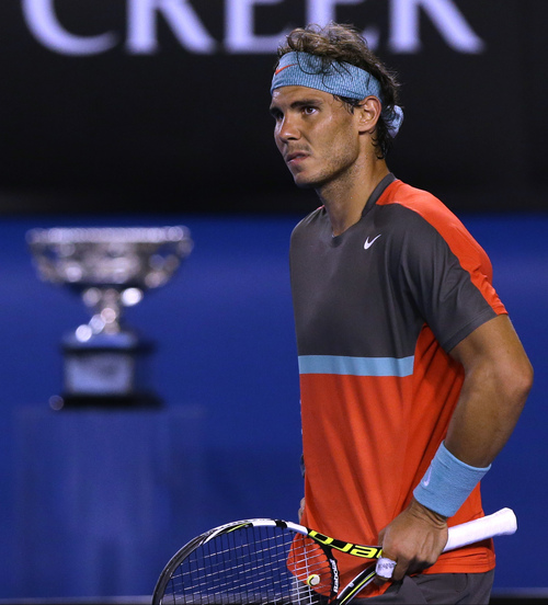 Rafael Nadal of Spain reacts as he plays Stanislas Wawrinka of Switzerland during the men's singles final at the Australian Open tennis championship in Melbourne, Australia, Sunday, Jan. 26, 2014. The championship trophy is seen at left. (AP Photo/Aaron Favila)