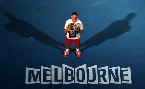 Stanislas Wawrinka of Switzerland holds the trophy after defeating Rafael Nadal of Spain in the men's singles final at the Australian Open tennis championship in Melbourne, Australia, Sunday, Jan. 26, 2014.(AP Photo/Eugene Hoshiko)