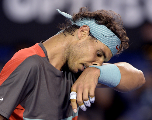 Rafael Nadal of Spain wipes the sweat from his face as he plays Stanislas Wawrinka of Switzerland during the men's singles final at the Australian Open tennis championship in Melbourne, Australia, Sunday, Jan. 26, 2014.(AP Photo/Andrew Brownbill)