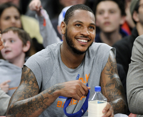 New York Knicks' Carmelo Anthony smiles as he watches from the bench during the fourth quarter of an NBA basketball game against the Charlotte Bobcats Friday, Jan. 24, 2014, at Madison Square Garden in New York. Anthony scored 62 points as the Knicks won 125-96. (AP Photo/Bill Kostroun)