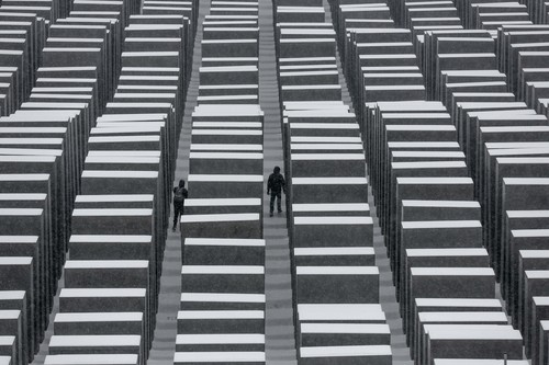 Two visitors walk inside the snow covered Holocaust Memorial at the International Holocaust Remembrance Day in Berlin, Monday, Jan. 27, 2014. The German parliament Bundestag will hold a special remembrance session at the Reichstag building in commemoration of the liberation of the Auschwitz death camp on Jan. 27, 1045. (AP Photo/Markus Schreiber)