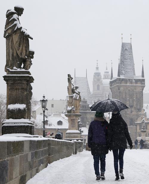 Tourists cross the medieval Charles Bridge as a snowfall hits Prague, Czech Republic, Monday, Jan. 27, 2014. (AP Photo/Petr David Josek)