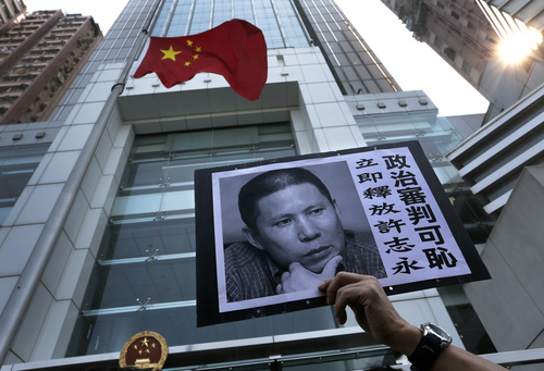"""A placard with a photo of legal scholar Xu Zhiyong is raised by a demonstrator protesting against a Chinese court's decision to sentence him in prison outside the Chinese liaison office in Hong Kong, Monday, Jan. 27, 2014. Xu was sentenced Sunday to four years in prison on the charge of disturbing order in public places. Xu's fledgling campaign became a target after it inspired people across the country to gather for dinner parties to discuss social issues and occasionally to unfurl banners in public places in small rallies. The placard reads: """"Release Xu Zhiyong immediately, shame on political trial."""" (AP Photo/Vincent Yu)"""