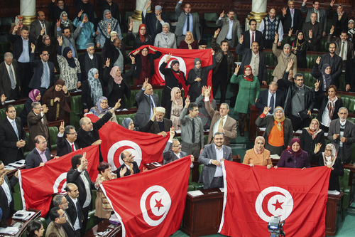 In this photo taken Sunday, Jan. 26, 2014, members of the Tunisian National Constituent Assembly celebrate the adoption of the new constitution in Tunis, Tunisia. After decades of dictatorship and two years of arguments and compromises, Tunisians on Sunday finally have a new constitution laying the foundations for a new democracy. The document is groundbreaking as one of the most progressive constitutions in the Arab world - and for the fact that it got written at all. It passed late Sunday by 200 votes out of 216 in the Muslim Mediterranean country that inspired uprisings across the region after overthrowing a dictator in 2011. (AP Photo/Aimen Zine)