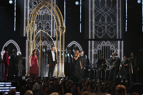 """Mary Lambert, from left foreground, Macklemore and Queen Latifah perform """"Same Love' on stage at the 56th annual Grammy Awards at Staples Center on Sunday, Jan. 26, 2014, in Los Angeles. (Photo by Matt Sayles/Invision/AP)"""