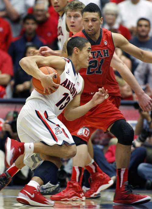 Arizona's Nick Johnson (13) drives with the ball into the defense of Utah's Jordan Loveridge (21) in the second half of an NCAA college basketball game on Sunday, Jan. 26, 2014, in Tucson, Ariz. (AP Photo/John Miller)
