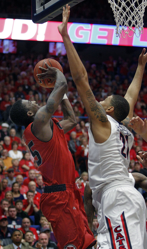 Utah's Delon Wright, left, shoots for two over the attempted defense of Arizona's Brandon Ashley (21) in the second half of an NCAA college basketball game on Sunday, Jan. 26, 2014 in Tucson, Ariz. (AP Photo/John Miller)