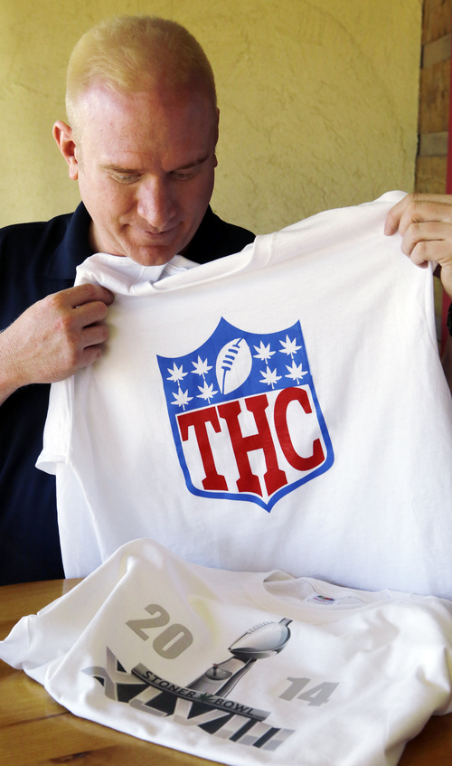 """Bryan Weinman is pictured with two of his """"Stoner Bowl"""" T-shirts in southeast Denver on Friday, Jan. 24, 2014.  Weinman and a few buddies registered the internet domain www.sonerbowl.org and are using the website to hawk T-shirts and hats celebrating the """"Stoner Bowl."""" One shirt features the Vince Lombardi Trophy, reserved for the game's victors, refashioned into a bong. Another displays a spoof of the league's logo, with the letters THC replacing NFL. (AP Photo/Ed Andrieski)"""