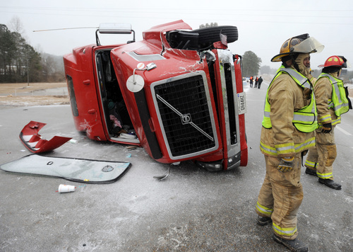Hattiesburg firefighters work the scene of a two-vehicle accident in the northbound lanes of U.S. 49 off of U.S. 98 in Hattiesburg Miss.,Tuesday,  Jan. 28, 2014. Icy roads were the cause of the accident that sent one person to the hospital with non-life threatening injuries.( AP Photo/Hattiesburg American, Ryan Moore)     NO SALES