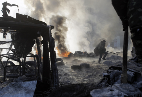 A protester walks near burning tires following clashes with police in central Kiev, Ukraine, Saturday Jan. 25, 2014. Ukraine's Interior Ministry has accused protesters in Kiev of capturing two of its officers as violent clashes have resumed in the capital and anti-government riots spread across Ukraine. (AP Photo/Darko Vojinovic)