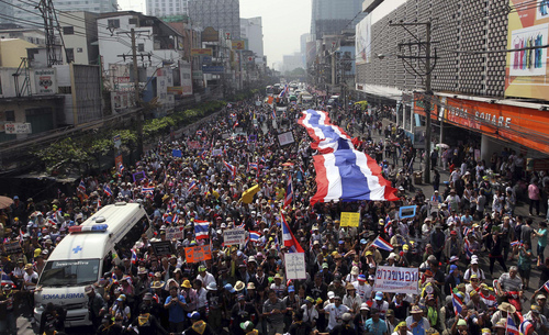 Thai anti-government protesters take to a street with a giant national flag during a march in Bangkok, Thailand Saturday, Jan. 25, 2014. Thailand's ruling party has questioned the reasoning behind a court decision allowing next month's general election to be postponed, but held open the possibility that it might agree to put off the polls if its political rivals agree to recognize the legitimacy of a new vote. (AP Photo/Apichart Weerawong)