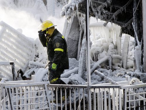 A police investigator walks through the icy rubble of a fire that destroyed a seniors' residence Friday, Jan. 24, 2014, in L'Isle-Verte, Quebec. Five people are confirmed dead and 30 people are still missing, while with cause of Thursday morning's blaze is unclear police said. Authorities are using steam to melt the ice and to preserve any bodies that are buried. (AP Photo/The Canadian Press, Ryan Remiorz)