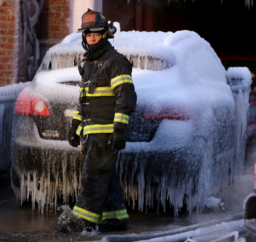 A North Hudson County Fire Department firefighter walks in front of an iced covered vehicle near a building where a a six-alarm fire was put out by officials, Friday, Jan. 24, 2014, in Union City, N.J. The fire began in one residential apartment building on 19th Street around 11:30 p.m. Thursday and quickly spread to two adjacent buildings. Approximately 50 residents, some wearing nothing more than robes and pajamas, were evacuated to a school that the Red Cross set up as a temporary shelter. (AP Photo/Julio Cortez)