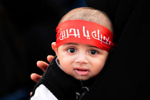 "A Bahraini baby wearing a headband that reads, ""I love you, oh Bahrain,"" sits on his mother's lap during a rally in Sitra, Bahrain, on Friday, Jan. 24, 2014. A few thousand people, many waving national flags, attended the rally organized by opposition groups calling for democracy in the Gulf island kingdom. (AP Photo/Hasan Jamali)"