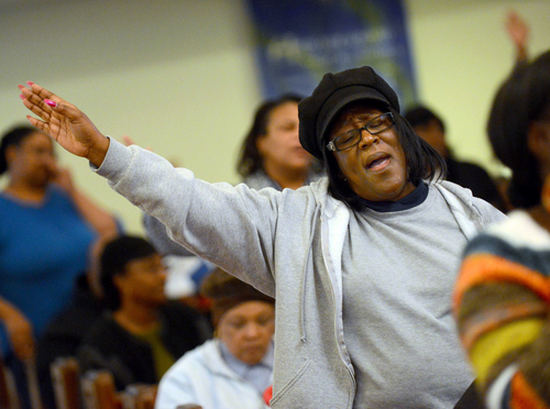 Barbara Allen raises her hands in prayer during the Concert of Prayer on Tuesday, Jan. 28, 2014, at Word Tabernacle Church in Rocky Mount, N.C. The local church community gathered together after the tragic shooting of four youths behind Word Tabernacle Church on Monday. (AP Photo/The Rocky Mount Telegram, Hannah Potes)