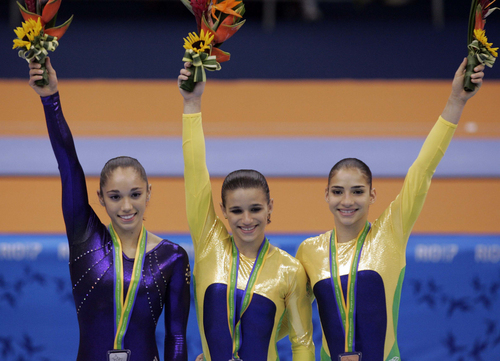 Winners of the women's pommel horse final react at Pan American Games gymnastics competition in Rio de Janeiro, Tuesday, July 17, 2007. From left is, United States silver medal winner Amber Trani, Brazil's gold medal winner Jade Barbosa and Brazil's bronze medal winner Lais Souza.  (AP Photo/Gregory Bull)