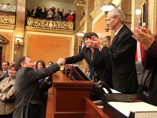 Utah Gov. Gary Herbert shakes hands with House Speaker Becky Lockhart, R-Provo, as Senate President Wayne Neiderhauser, R-Sandy, applauds prior to the State of the State speech to the Utah State Legislature on Capitol Hill, Wednesday, January 30, 2013, in Salt Lake City. (AP Photo/Tom Smart,Pool)