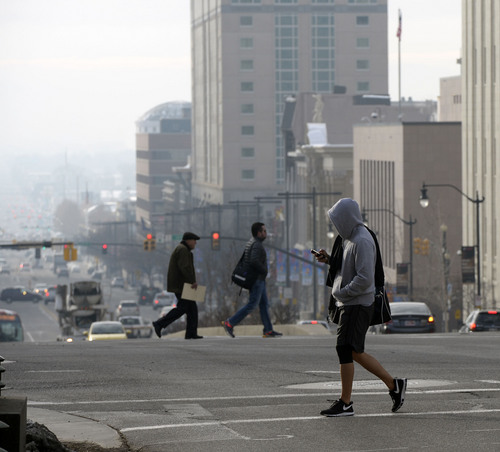 Al Hartmann  |  The Salt Lake Tribune Pedestrians walk across State Street and South Temple in dowtntown Salt Lake City Monday morning December 30 as pollution increases in the valley.  The Utah Division of Air Quality rated the air in the orange range with a health advisory for elderly and persons with existing heart or lung disease to stay indoors and reduce physical activity.