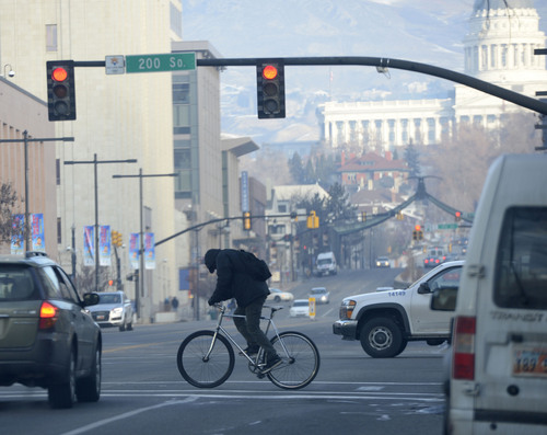 Al Hartmann  |  The Salt Lake Tribune A bicyclist rides in downtown Salt Lake City Monday morning December 30 as unhealthy air increases. The Utah Division of Air Quality rated the air in the orange range with a health advisory for elderly and persons with existing heart or lung disease to stay indoors and reduce physical activity.