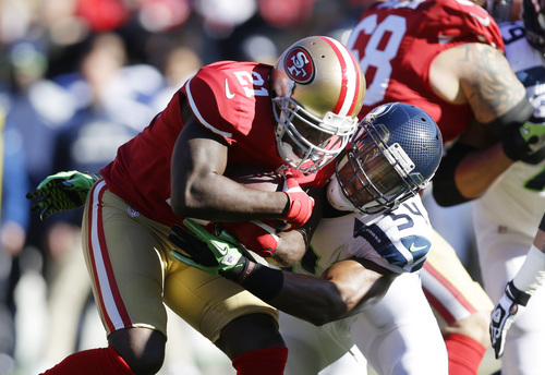 San Francisco 49ers running back Frank Gore (21) is tackled by Seattle Seahawks' middle linebacker Bobby Wagner (54) in the first half of an NFL football game on Sunday, Dec. 8, 2013, in San Francisco. (AP Photo/Marcio Jose Sanchez)