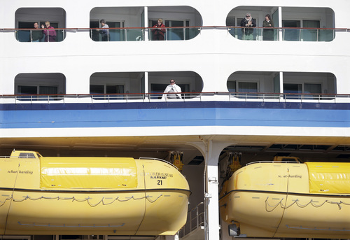 People look out from the Explorer of the Seas cruise ship as it docks at a berth, Wednesday, Jan. 29, 2014, in Bayonne, N.J. The number of passengers and crew reported stricken ill on the cruise ship has risen to nearly 700. The U.S. Centers for Disease Control and Prevention said Wednesday its latest count puts the number of those sickened aboard the Explorer of the Seas at 630 passengers and 54 crew members. (AP Photo/Mel Evans)