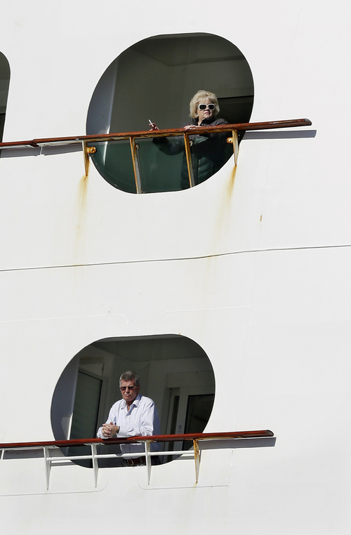 People look out from the Explorer of the Seas cruise ship as it docks at a berth, Wednesday, Jan. 29, 2014, in Bayonne, N.J.. The number of passengers and crew reported stricken ill on the cruise ship has risen to nearly 700. The U.S. Centers for Disease Control and Prevention said Wednesday its latest count puts the number of those sickened aboard the Explorer of the Seas at 630 passengers and 54 crew members. (AP Photo/Mel Evans)